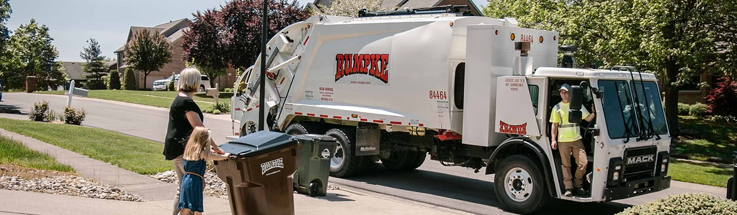 Garbage truck driver picking up trash and recycling from neighborhood